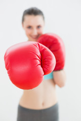 Blurred smiling woman in red boxing gloves