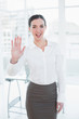 Elegant businesswoman waving hand in office