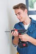 Handsome handyman using a drill