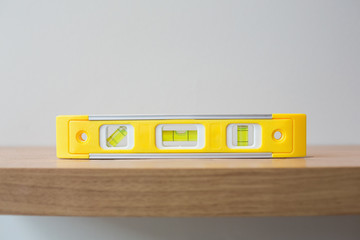 Spirit level on wooden surface against the wall