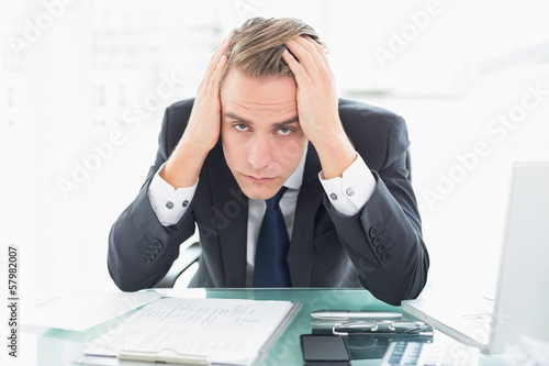 Worried businessman sitting at office desk