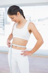 Woman measuring waist in fitness studio