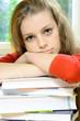 Schülerin überfordet auf Buch-Stapel
