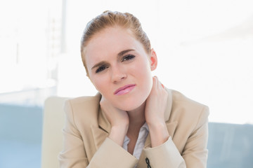 Close up of young businesswoman with neck pain