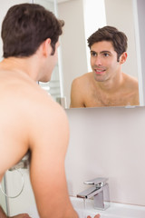 Rear view of a young smiling at self in bathroom mirror