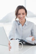 Businesswoman with laptop and diary in office