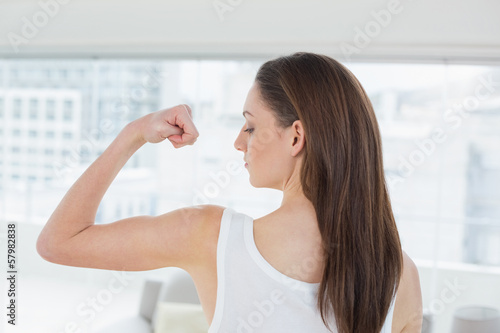 Fit brown haired woman flexing muscle in fitness studio