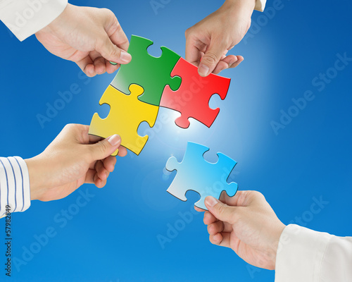 Team work concept, Hands hold puzzles with clear blue sky and su