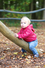 Cute little baby girl plays in wooden playground in the forest