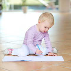 Cute toddler draws with colorful pencils sitting on tiles floor