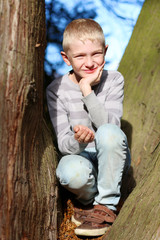 Happy teenager boy sitting on the tree between the branches