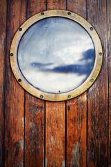 Porthole ship window on wooden doors, sky reflection