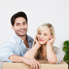 glückliches paar stützt sich auf umzugskarton