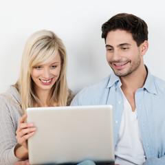 glückliches paar schaut zusammen auf laptop
