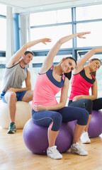 Sporty people stretching hands on exercise balls at gym