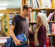 Smiling young couple against bookshelf in library