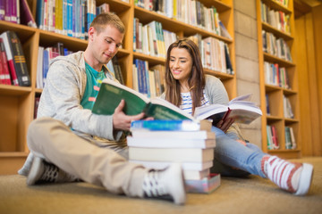 Students reading books on library floor
