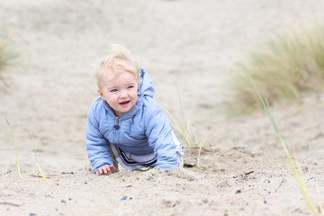 Happy blonde toddler girl plays in the dunes