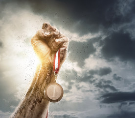 Success, male hand holding gold medal against the dramatic sky
