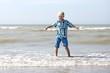 Happy beautiful teenager boy has fun playing on the beach
