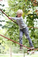 Sportive teenager boy climbs on the ropes at playground