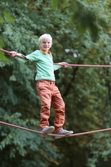 Happy teenager boy climbs on the ropes at playground