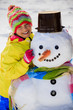 Winter fun, happy kid playing with snowman