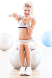 Fototapety Woman lifting dumbbells while sitting on a fitness ball