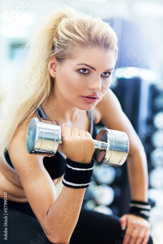 Woman in gym lifting weights - 57990441