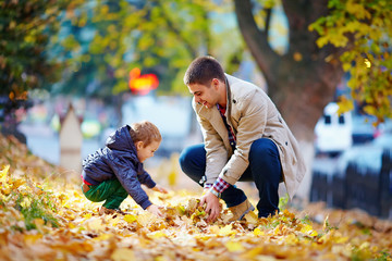 happy father and son having fun in autumn park
