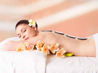 woman relaxing in spa salon with hot stones