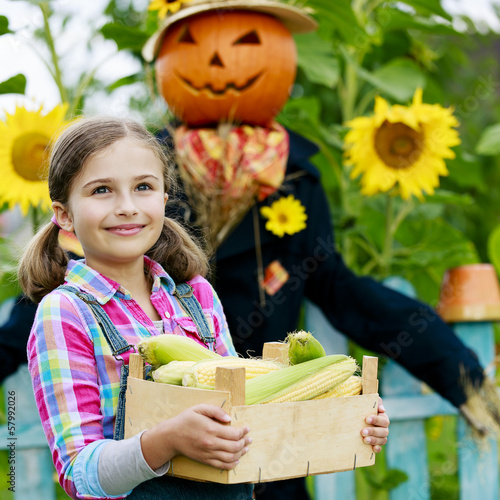 Scarecrow and happy girl  in the garden - harvest