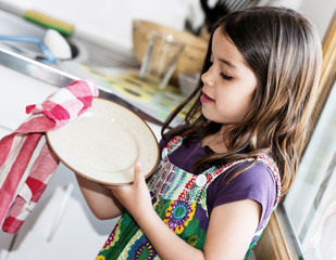 Expressive portrait of very cute girl wiping the dishes