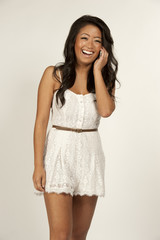 Cute girl wearing a white lace romper laughing