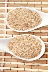 wheat bran on white ceramic spoon