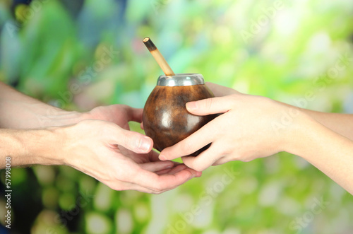 Woman hands giving calabash and bombilla with yerba mate,