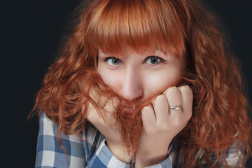 frightened red-haired girl hides her face in her hair
