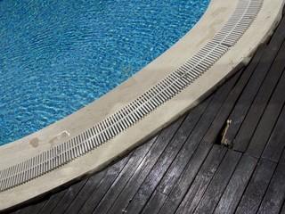 Dunkelbraune Schiffsdielen an einem hellblauen Swimmingpool