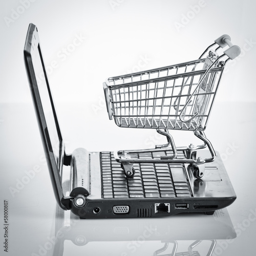 Online shopping. Shopping cart with notebook on the white. shopp