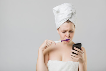 young girl watching her phone uncertainly while brushing her tee