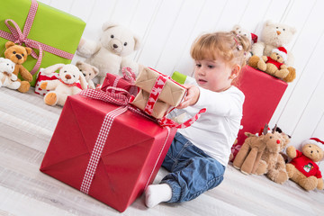 Kleines Mädchen packt ein rotes Geschenk aus - Freude