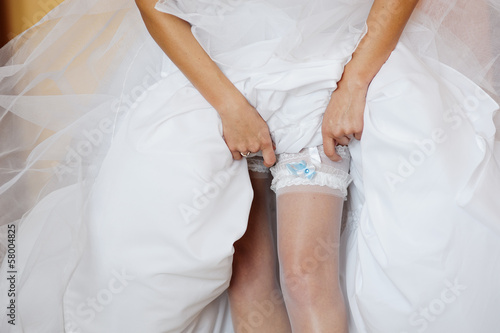 A bride is tidying the garter up on stockings