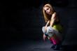 Woman posing in dark urban environment