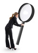 Woman looking through a giant magnifying glass