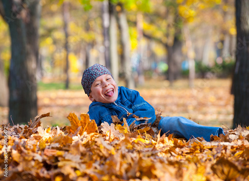 boy lies on yellow leaves in autumn park