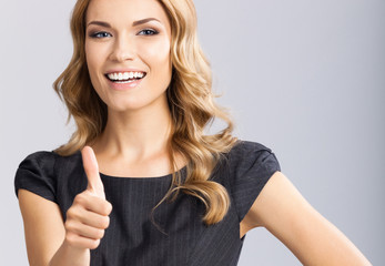 Businesswoman with thumbs up gesture, on gray