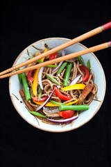 Buckwheat noodles with chicken and vegetables on black