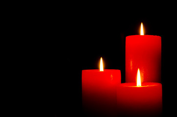 Three red burning candles with black background