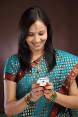 Smiling young traditional woman text messaging