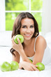 Young happy smiling woman with apples, indoors